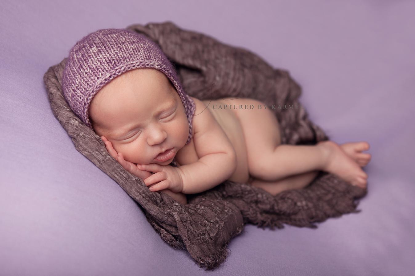 newborn sleeping on purple backdrop