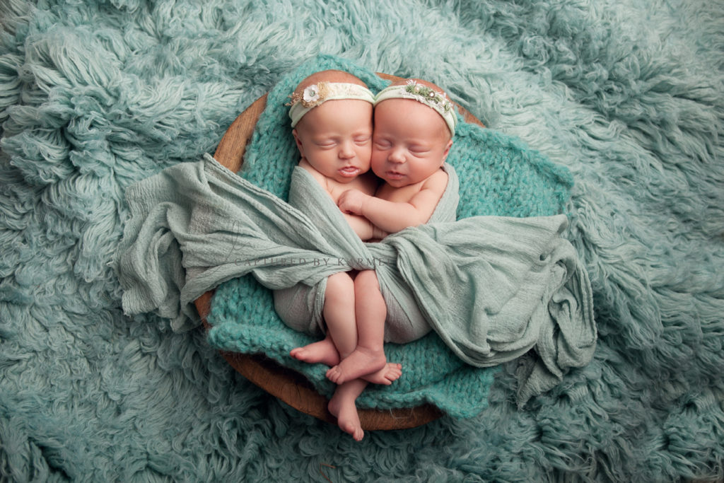 identical twins wrapped together and asleep for photo session