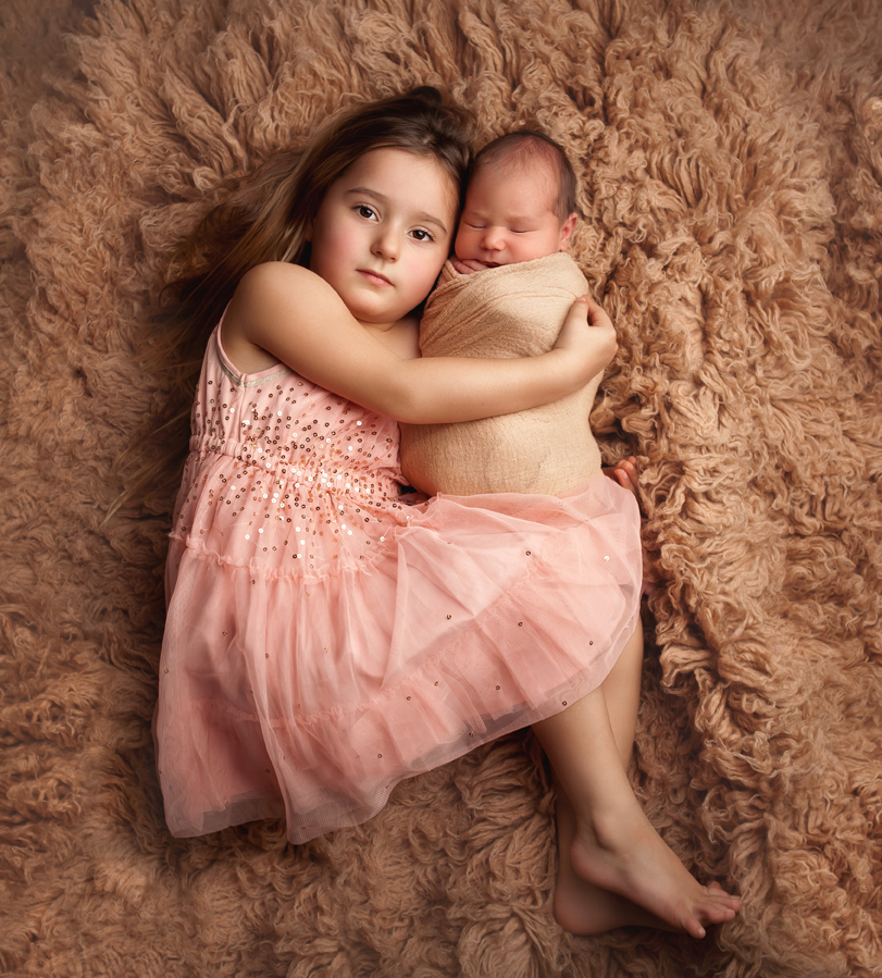 newborn sibling on grey rug photo